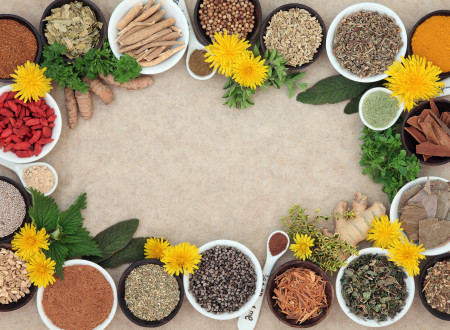 Herbal medicine selection with fresh and dried herbs and spices forming an abstract background on natural hemp paper.